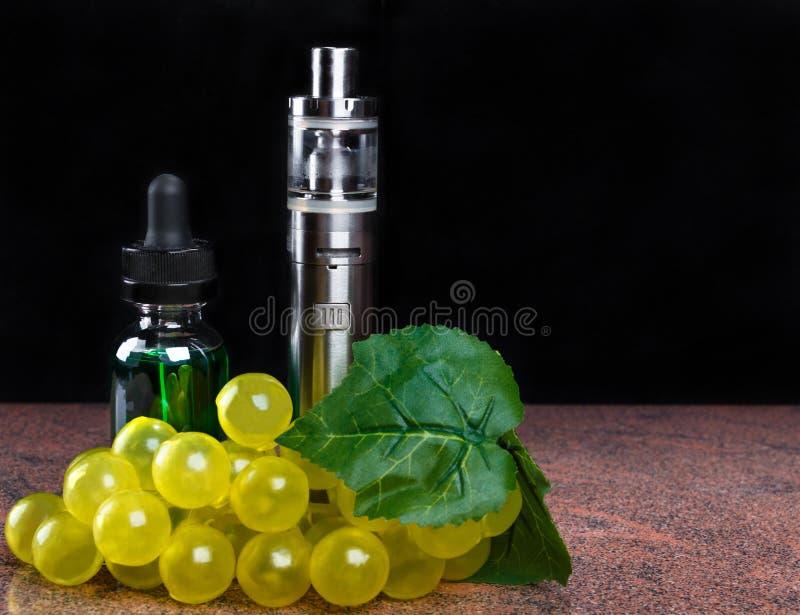 Elektroniczny papieros, butelka z vape cieczem i wiązka winogrona z liściem na czarnym tle, fotografia royalty free