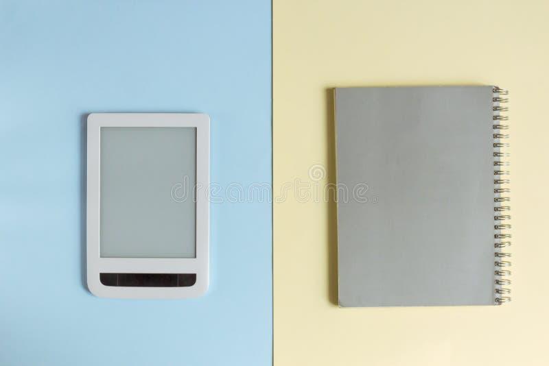 Elektroniczny pastylki, papieru notatnik na pastelowych tło i, pojęcie wybór między starym i nowym obraz stock