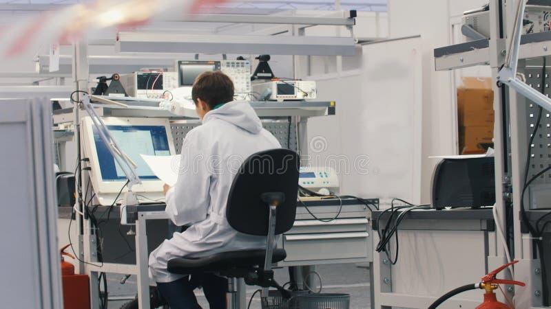 Elektronika inżyniery pracuje w lab Inżyniery siedzi przy działaniem na komputerze i stołem widok z powrotem zdjęcia stock