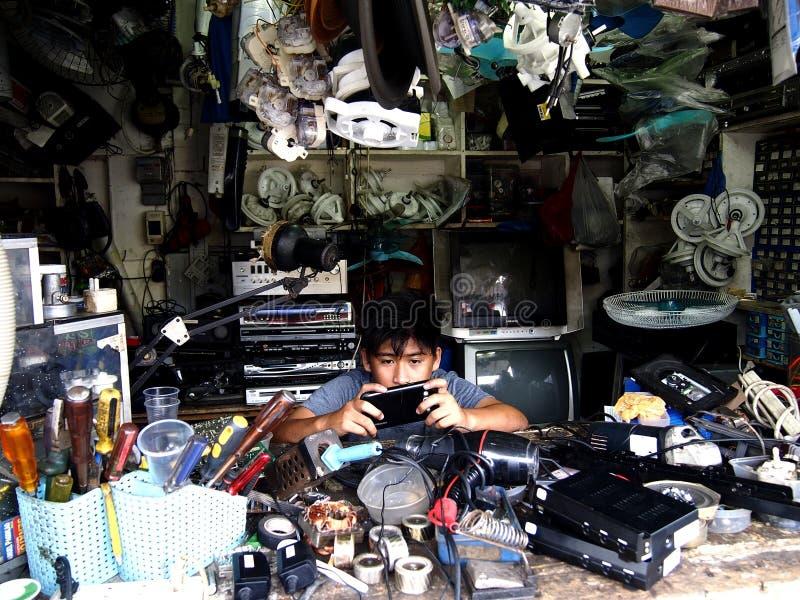 Elektronika remontowego sklepu technik bawić się z jego telefonem komórkowym obraz royalty free