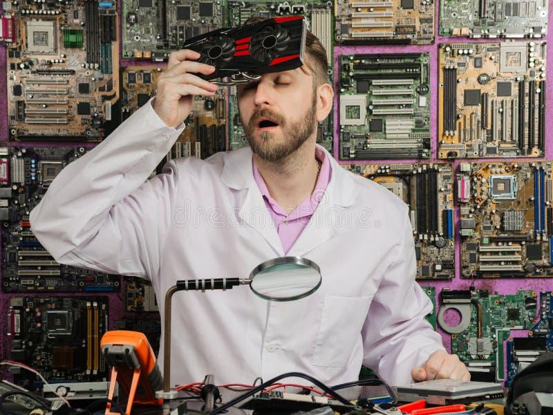Elektronikteknikern kyler hans panna med en datorkylare, medan sitta på hans labbtabell royaltyfri bild