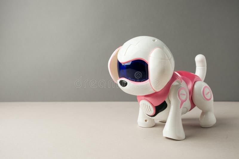Elektronisch interactief stuk speelgoed hondpuppy op een grijze achtergrond, geavanceerd technisch concept, huisdier van het toek stock foto