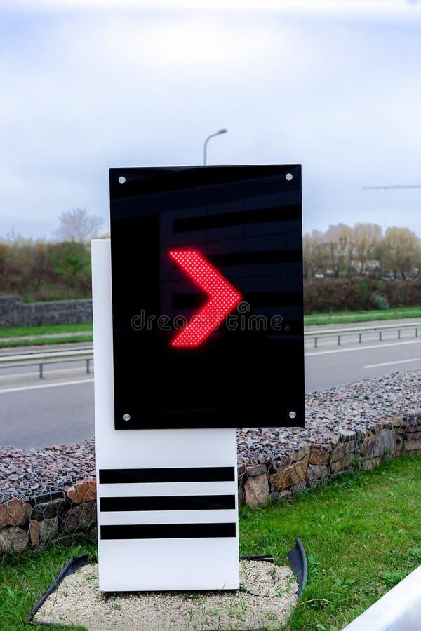 Elektronisch scorebord met rode pijlwijzer op benzinestation stock foto's
