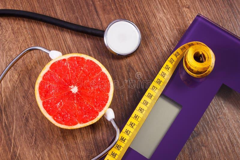 Elektronische badkamersschaal, centimeter en verse grapefruit met stethoscoop, vermageringsdieet en gezonde levensstijlen stock afbeelding