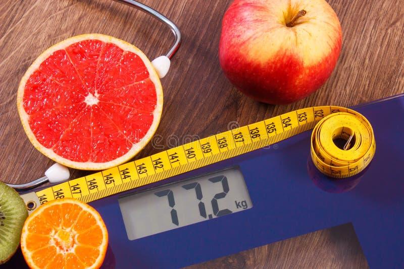 Elektronische badkamersschaal, centimeter en verse vruchten met stethoscoop, vermageringsdieet en gezonde levensstijlen royalty-vrije stock afbeeldingen