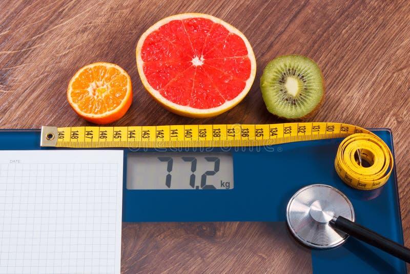 Elektronische badkamersschaal, centimeter en verse vruchten met stethoscoop, vermageringsdieet en gezonde levensstijlen stock fotografie