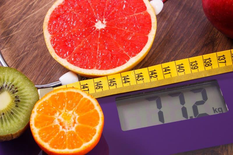 Elektronische badkamersschaal, centimeter en verse vruchten met stethoscoop, vermageringsdieet en gezonde levensstijlen stock afbeelding