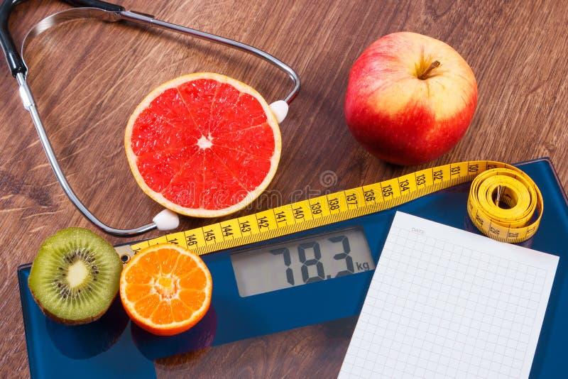 Elektronische badkamersschaal, centimeter en verse vruchten met stethoscoop, vermageringsdieet en gezonde levensstijlen royalty-vrije stock afbeelding