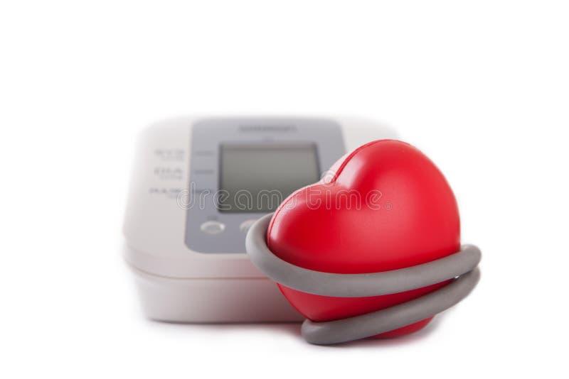 elektronische bloeddrukmeter en rood hart stock afbeelding