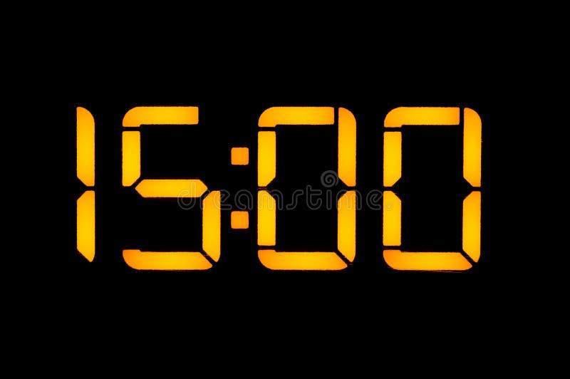 Elektronische Digitaluhr mit gelben Zahlen auf einem schwarzen Hintergrund zeigt der Zeit fünfzehn null nulluhr Isolat, Nahaufnah lizenzfreie stockbilder