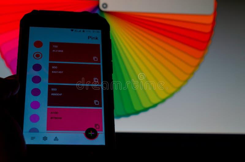 Elektronische Farbpaletten zwischen einem Smartphone und einem Laptop stockbilder