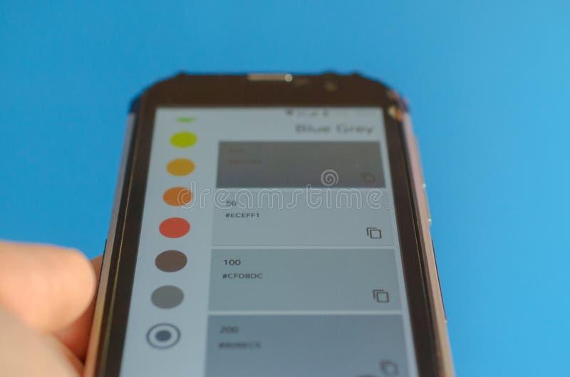 Elektronische Farbpaletten zwischen Smartphone und blauem Hintergrund lizenzfreies stockfoto