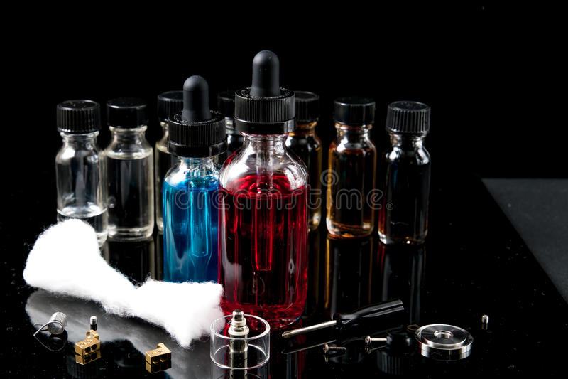 Elektronische sigaretvloeistoffen met rook op zwarte achtergrond royalty-vrije stock afbeeldingen