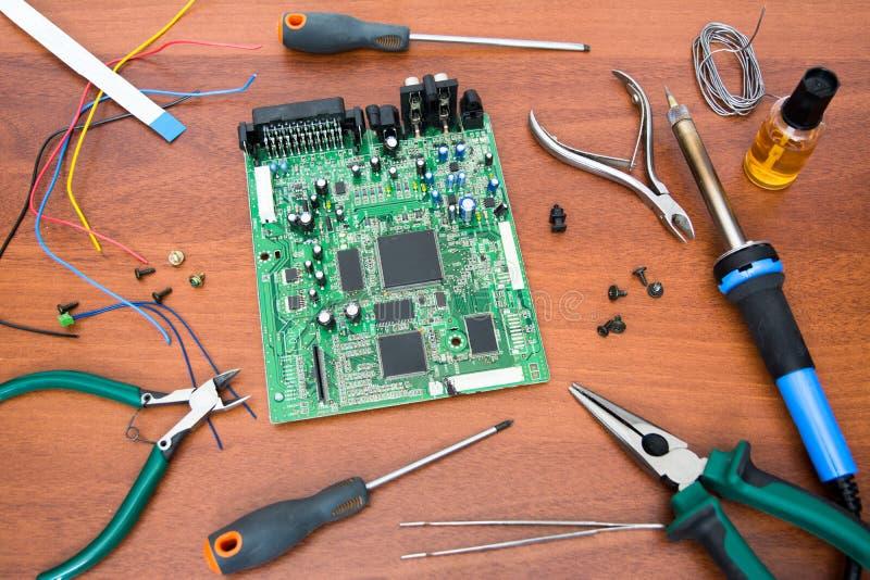 Elektronische Systemplatine mit Mikrokreisläufen und elektronische Bauelemente Notwendige Werkzeuge für Reparatur stockfotos