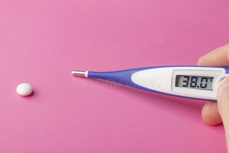 Elektronische thermometer en pil op een roze achtergrond 38 graden op hoge temperatuur van Celsius op vertoning stock fotografie