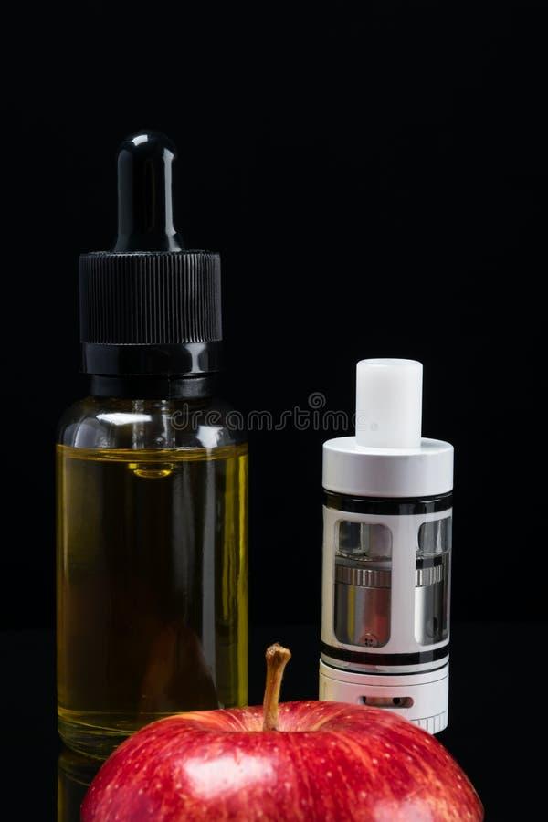 Elektronische Zigarette und Flüssigkeit mit einem Geschmack eines roten Apfels auf einem schwarzen Hintergrund stockbilder