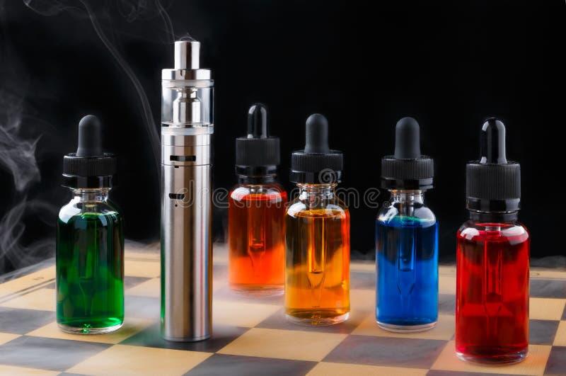 Elektronische Zigarette und Flaschen mit vape Flüssigkeit innerhalb des Dampfes auf Schachbrett und schwarzem Hintergrund stockfoto
