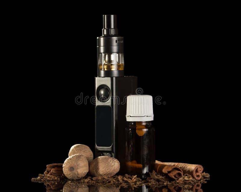 Elektronische Zigarette und Krumen des Tabaks, Flüssigkeit für das Rauchen, Gewürze, lokalisiert auf einem Schwarzen lizenzfreies stockfoto