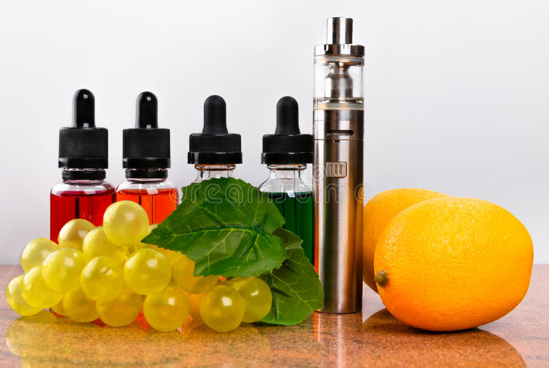 Elektronische Zigarette, Zitronen und Weintraube auf Granitoberfläche und weißem Hintergrund stockfotografie