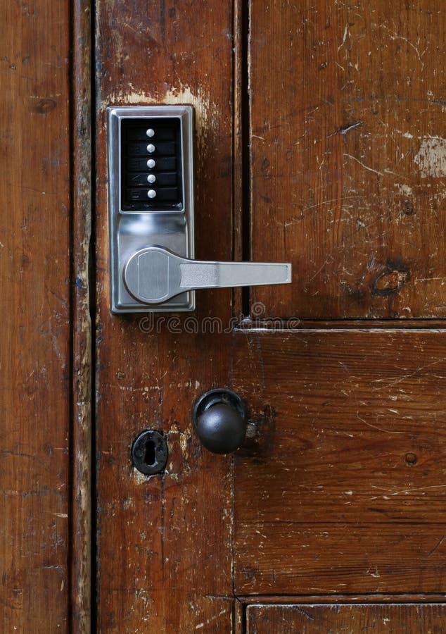 Elektronischer Türgriff mit numerischen Knöpfen auf alter Tür stockbild