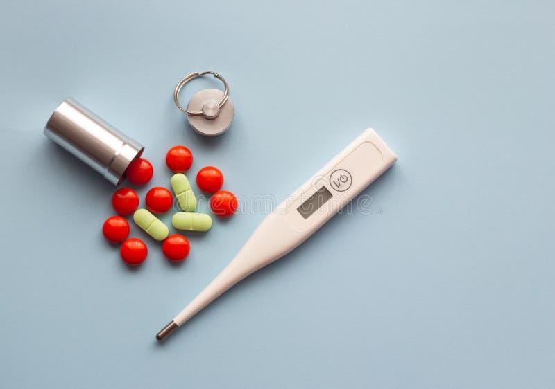 Elektronischer Thermometer und farbige Pillen auf einem blauen Hintergrund stockbilder