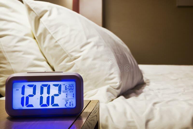 Elektronischer Wecker steht auf einem Nachttisch im Raum lizenzfreies stockbild
