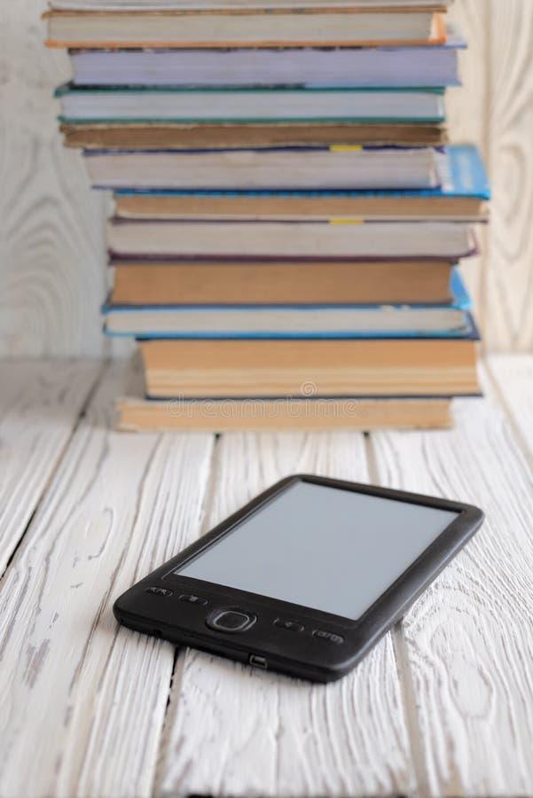 Elektronisches Buch gezeigt gegen einige regelmäßige Lehrbücher stockfoto
