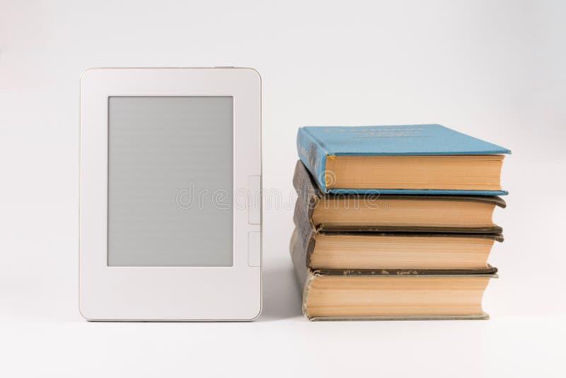 Elektronisches Buch mit Stapel regelmäßigen alten Büchern lokalisiert auf Weiß lizenzfreies stockbild