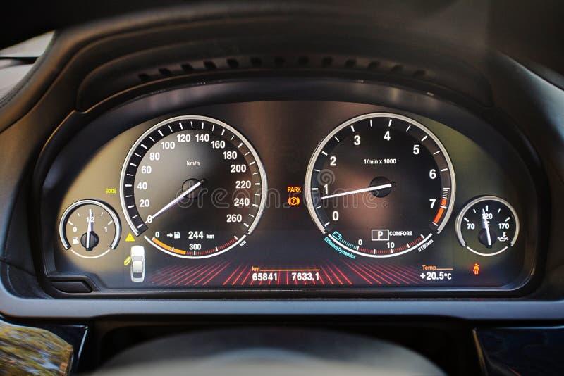 Elektronisk instrumentbräda av den moderna lyxiga bilen med elektronisk skärm och med den vita pilhastighetsmätaretakometern och  arkivfoto