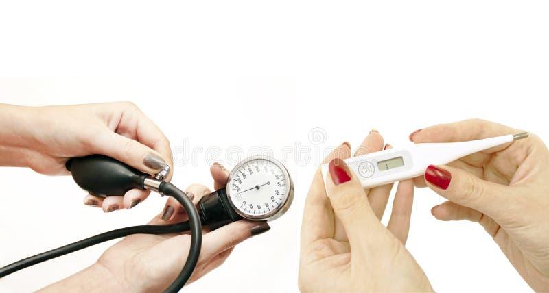 Elektronisk termometer och blodtryck i kvinnors händer royaltyfri bild
