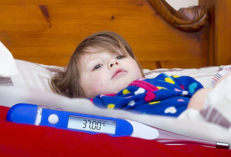 Elektronisk termometer och lite sjuk flicka arkivbilder