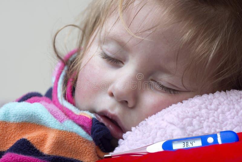 Elektronisk termometer och lite sjuk flicka royaltyfri foto