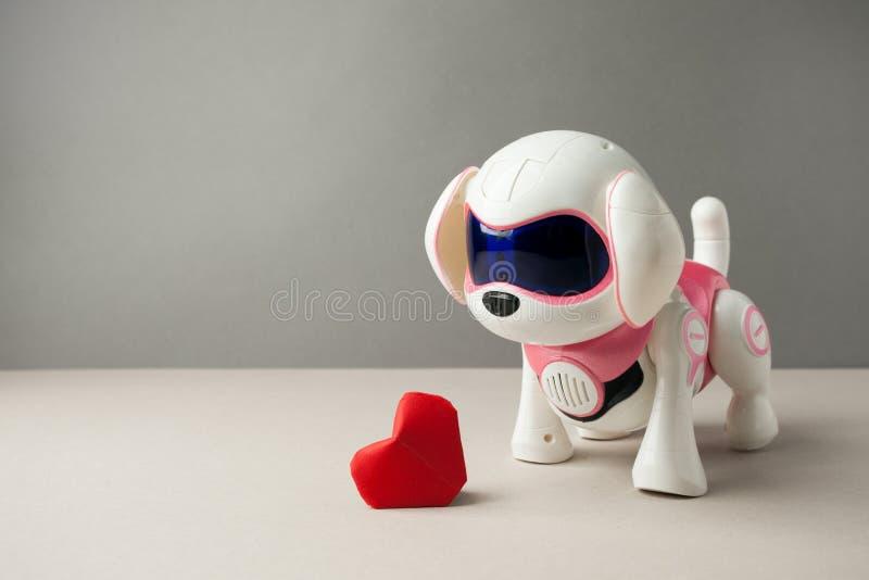 Elektronisk växelverkande valp för leksakhund med röd pappers- origamihjärta på en grå bakgrund, tekniskt avancerat begrepp, husd arkivbilder