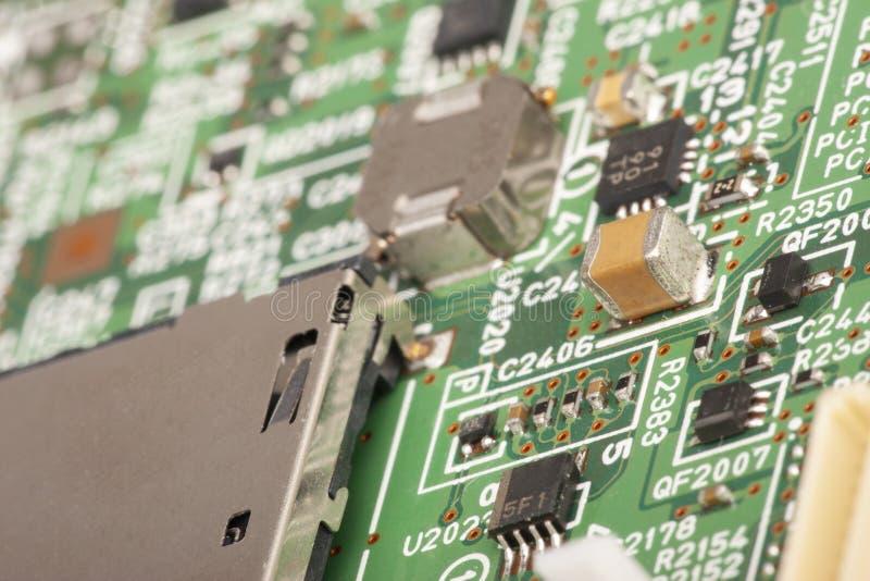 elektroniskt bräde Brädet presenterar beståndsdelar: chiper dioder, kondensatorer, kvävningar grunt djupfält royaltyfri foto
