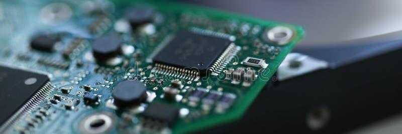 Elektroniskt bräde med mikrochipers på en hårddiskbakgrund royaltyfri foto