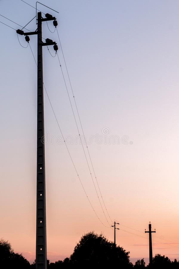 Elektropijlers op zonsondergang stock afbeeldingen