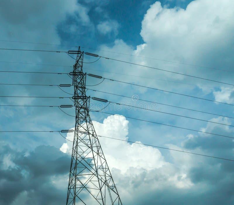 Elektropolen van hoogspanning in witte wolk en blauwe hemel/de de elektrische lijnen en draden van de poolmacht met blauwe hemel/ royalty-vrije stock foto