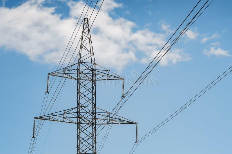 Elektrotorenpyloon en draden op een blauwe hemel met wolken stock afbeelding