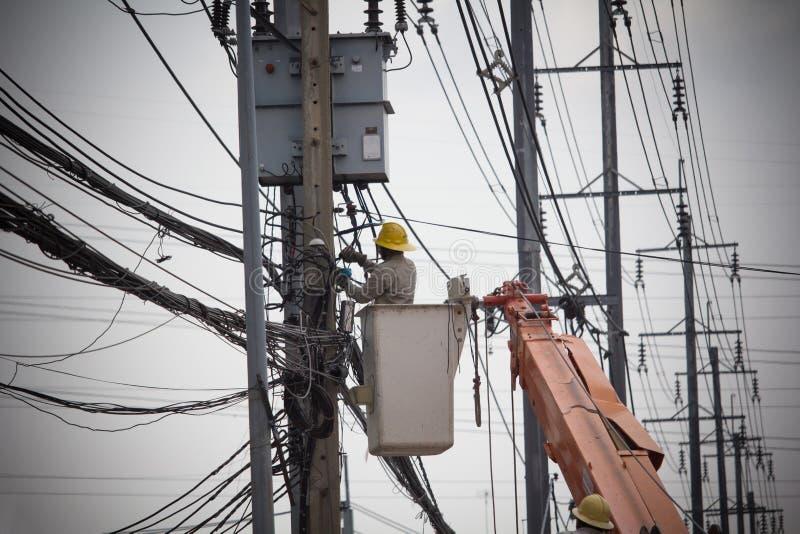 Elektrycy Depeszuje Kablowe remontowe usługi Technik sprawdza naprawianie łamającego elektrycznego drut na słupie fotografia stock