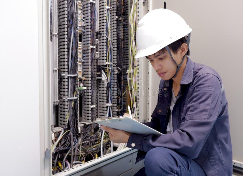 Elektrycy ono uśmiecha się, sprawdzać elektrycznych pudełka w przemysłowej fabryce obraz stock