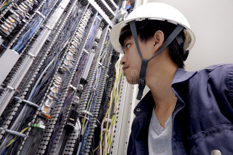 Elektrycy ono uśmiecha się, sprawdzać elektrycznych pudełka w przemysłowej fabryce zdjęcia stock