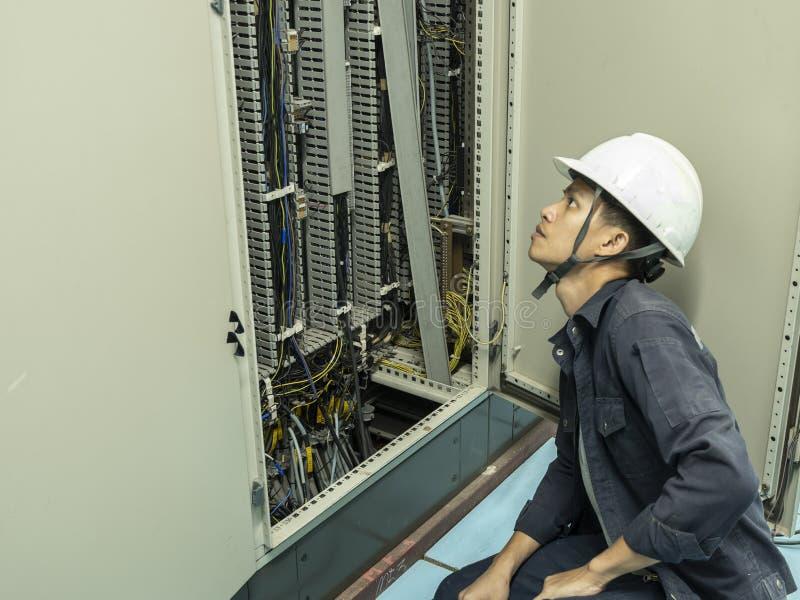 Elektrycy sprawdzają elektrycznych pulpit operatora w przemysłowych roślinach obrazy stock