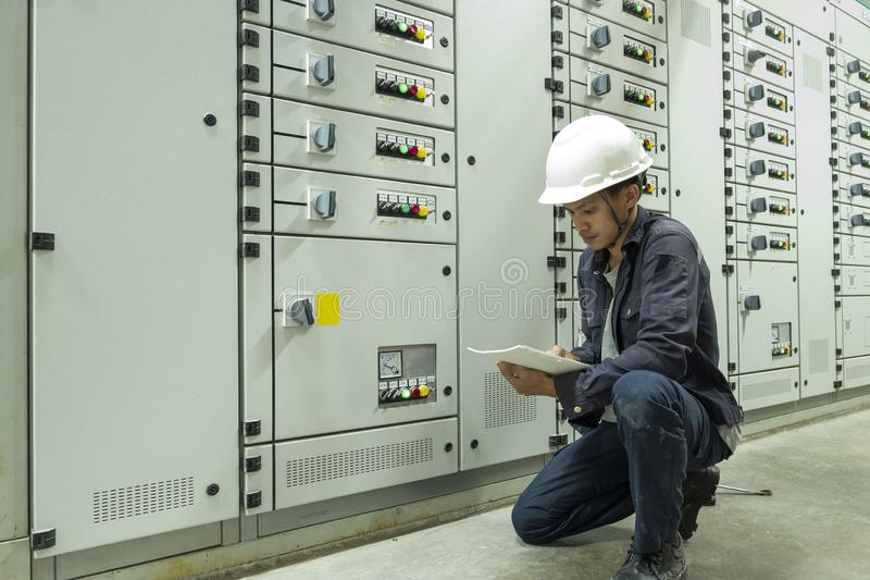 Elektrycy sprawdzaj? elektrycznych pulpit operatora w przemys?owych ro?linach obrazy royalty free