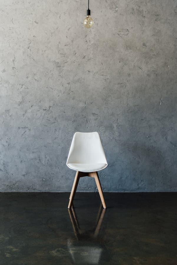 Elektryczna żarówka i nowożytny biały krzesło na podłoga fotografia stock