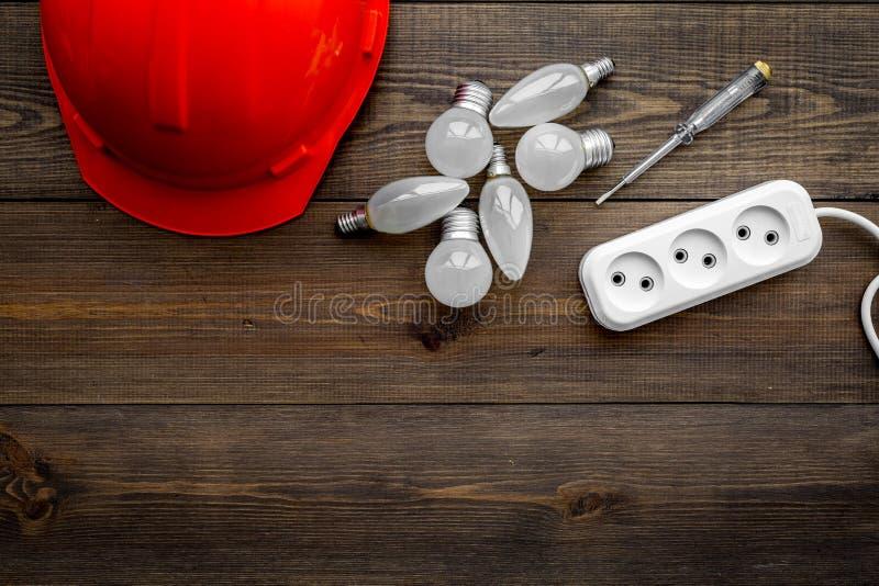 Elektryczna instalacja, depeszuje pracy pojęcie Ciężki kapelusz, żarówka, gniazdkowy ujście na ciemnej drewnianej tło odgórnego w obraz royalty free