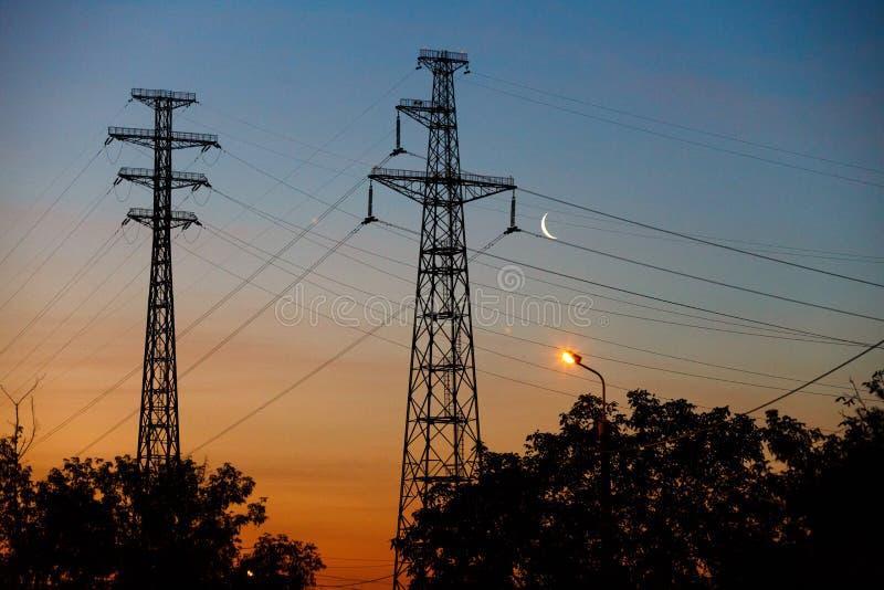 Elektryczne linie pod nocnym niebem z księżyc zdjęcie royalty free