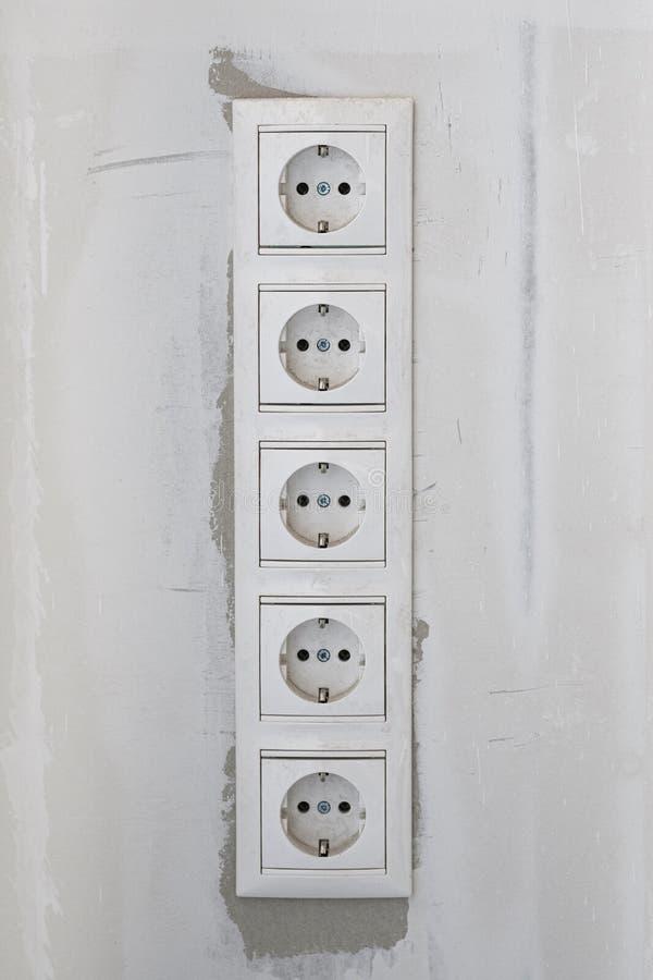 Elektryczne nasadki na biel ścianie Pusty, niezatamowany europejski ścienny ujście zamknięty w górę popielatego tła na, zdjęcie royalty free