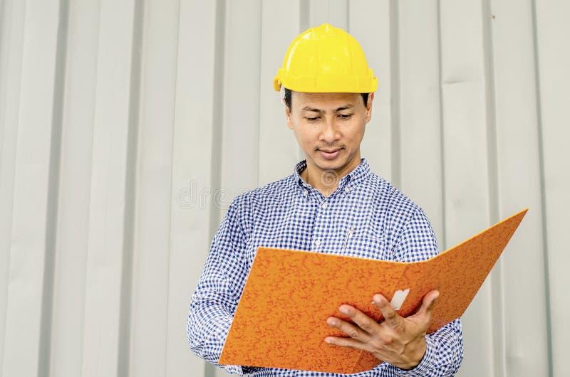 Elektrycznego inżyniera mienia kartoteki podczas gdy będący ubranym osobistego ochronnego wyposażenia zbawczego hełm przy budową zdjęcia stock