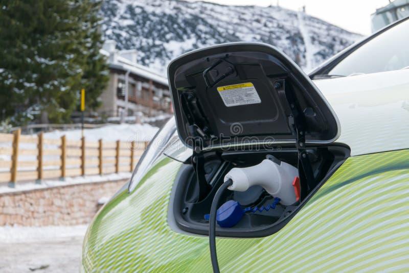 Elektrycznego samochodu wtyczkowy ładować w zimy góry miasteczku fotografia stock