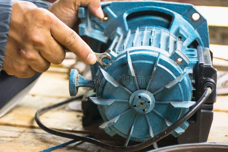 Elektrycznego silnika i mężczyzna wyposażenia pracująca naprawa na drewnianym podłogowym tle Tła wyposażenie lub mechanik obrazy royalty free